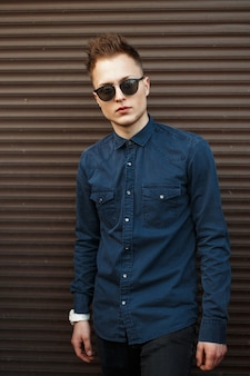 Homme à la mode élégant dans des lunettes de soleil et une chemise près d'un mur métallique