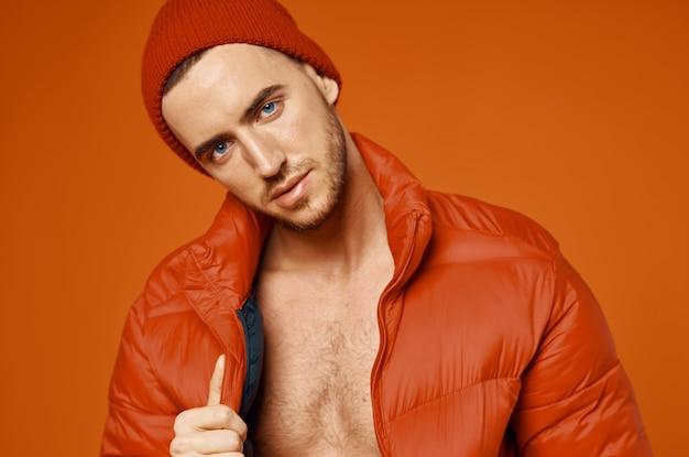 Homme à la mode en veste rouge corps nu studio fond orange