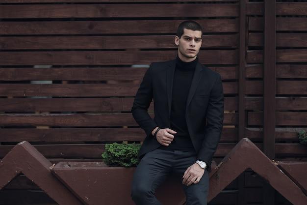 Homme à la mode, vêtu d'un costume, assis contre le mur en bois
