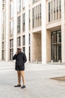 Homme moderne à l'aide de son téléphone à l'extérieur