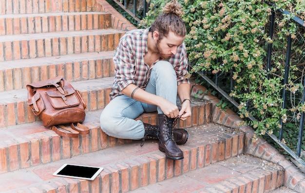 Homme moderne attachant des chaussures dans les escaliers