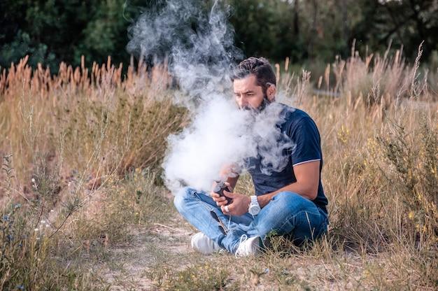 Homme moderne bénéficiant d'une e-cigarette. l'homme aime vraiment le processus de fumer.