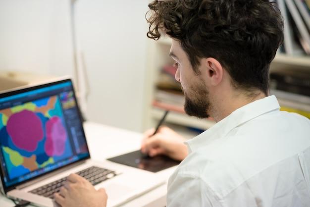 Homme moderne hipster beau travail à la maison en utilisant un ordinateur portable