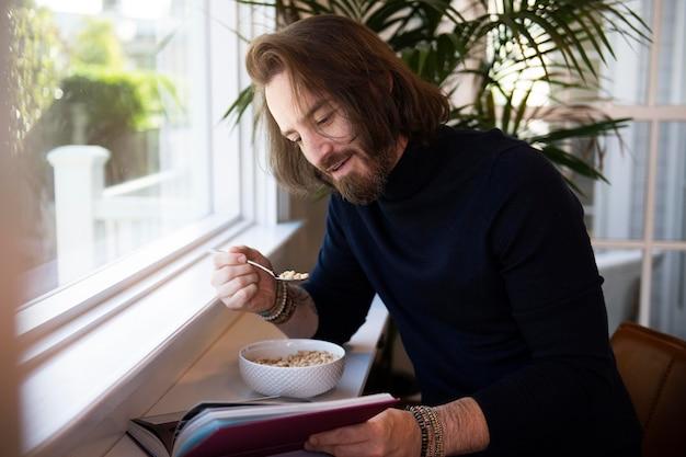 Homme moderne lisant tout en prenant son petit déjeuner