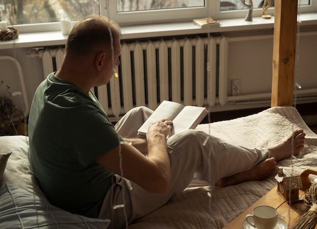 Homme moderne mature assis sur le lit et livre de lecture, vue latérale ou arrière.