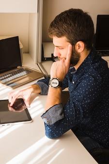 Homme moderne pensif à l'aide de tablette numérique