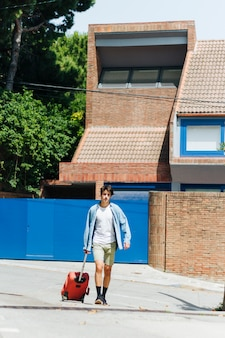 Homme moderne avec sac à main marchant dans la rue