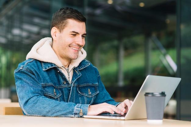 Homme moderne utilisant un ordinateur portable en milieu urbain