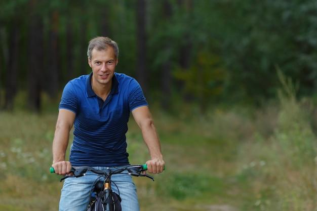 L'homme monte à vélo dans la forêt de pins, loisirs sportifs