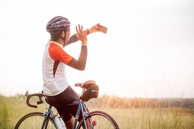 Un homme monté sur un vélo de sport vintage pour l'exercice du soir. un homme fait du vélo pour respirer l'air frais au milieu de la nature, de la prairie, de la forêt, avec le soleil du soir qui brille. un homme prenant un selfie à vélo.