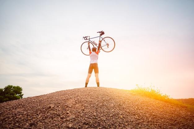 Un homme monté sur un vélo de sport vintage pour l'exercice du soir. un homme soulevant un vélo dans l'atmosphère du soir. un homme fait du vélo sur la montagne.