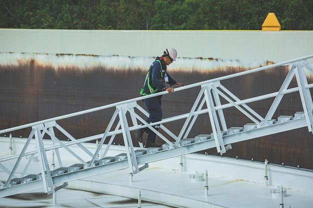 Homme monter l'huile de réservoir d'inspection visuelle de toit de stockage d'escalier