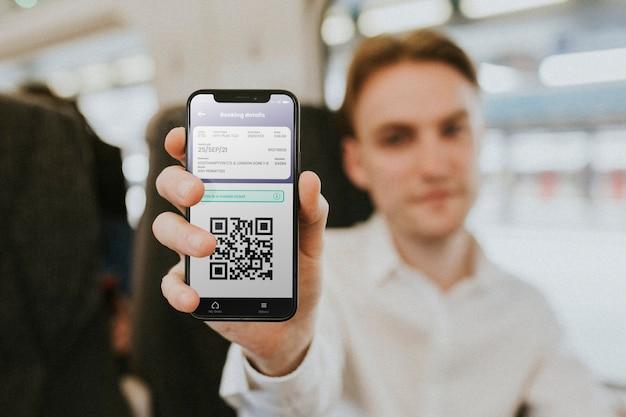 Homme montrant une application pour smartphone avec un billet réservé