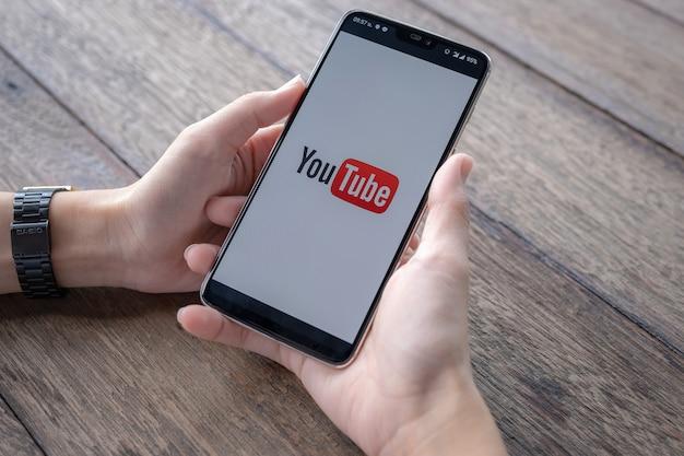 Homme montrant une application youtube sur un smartphone