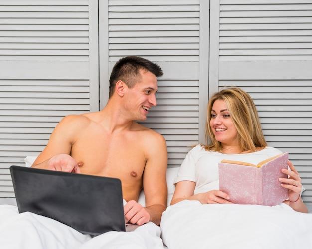 Homme montrant un écran d'ordinateur portable à une femme au lit