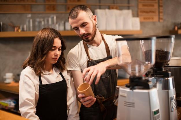 Homme montrant à une femme une tasse avec une machine à café