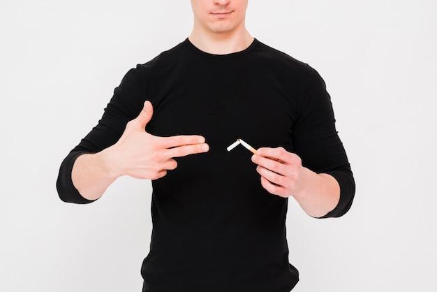 Homme montrant un geste de pistolet près de la cigarette cassée