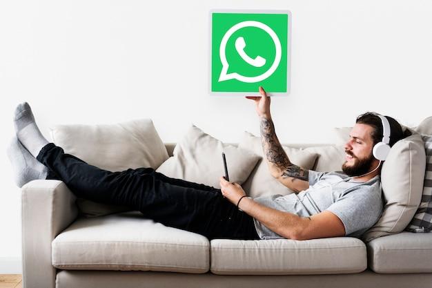 Homme montrant une icône whatsapp messenger
