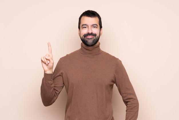 Homme montrant et en levant un doigt en signe du meilleur