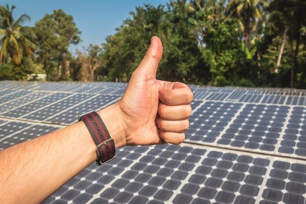 Homme montrant les pouces vers le haut à la centrale solaire, se sentant à l'objectif d'une grande énergie de performance