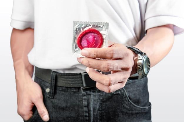 Homme montrant un préservatif