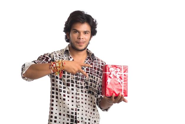 Homme montrant rakhi sur sa main avec des sacs à provisions et une boîte-cadeau à l'occasion du festival raksha bandhan.