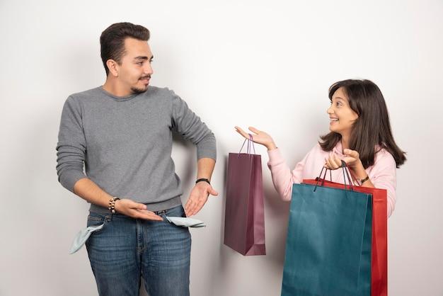 Homme montrant sa poche pour ne pas avoir d'argent à son amant.