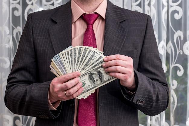 Homme montrant son profit en billets en dollars