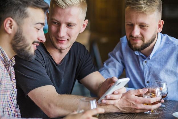 Homme montrant un téléphone portable à ses amis masculins