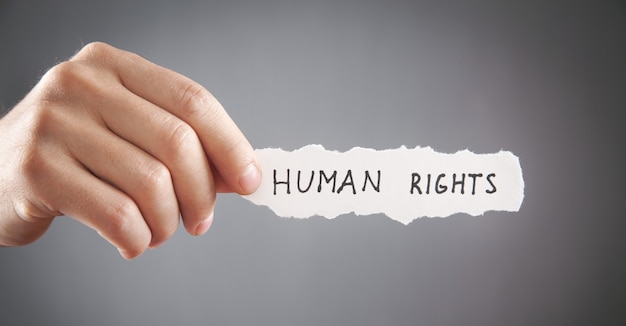 Homme montrant le texte des droits de l'homme sur du papier déchiré.