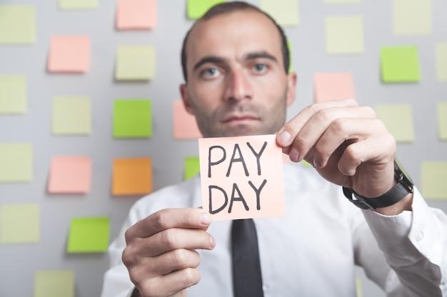 Homme montrant le texte du jour de paie sur pense-bête.