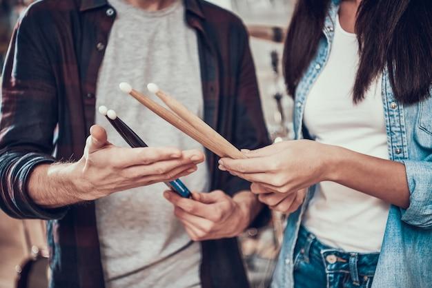 Un homme montre des baguettes à une fille dans un magasin de musique.