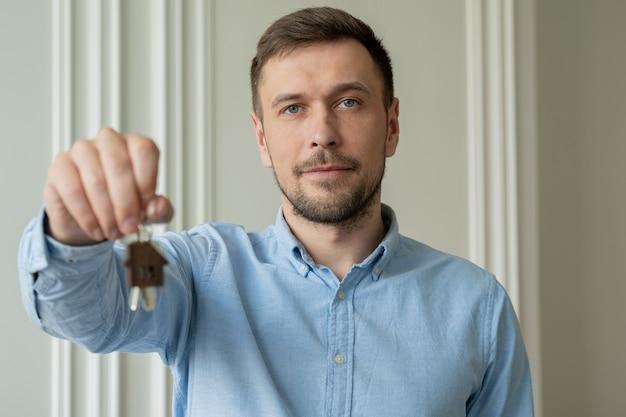 L'homme montre les clés de son nouvel appartement dans le salon