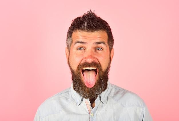 L'homme montre les émotions des gens de la langue face à l'expression de l'homme fanny heureux homme barbu homme barbu avec de longs