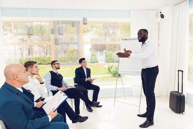 L'homme montre quelque chose à ses collègues dans la salle d'attente.