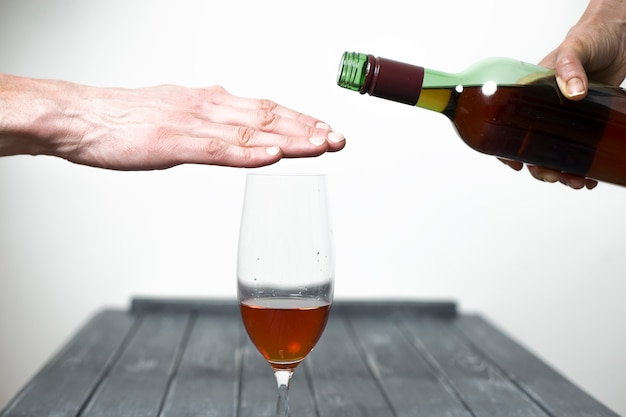 Un homme montre à sa main son refus de boire du vin.