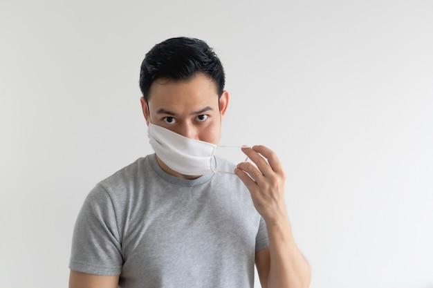 L'homme montre son masque et comment le porter isolé