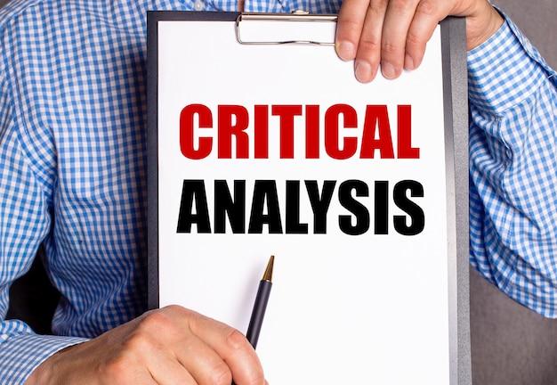 L'homme montre avec un stylo le texte analyse critique sur une feuille blanche.