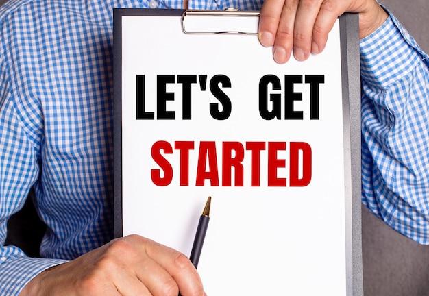 L'homme montre avec un stylo le texte let is get started sur une feuille blanche