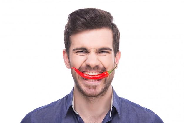 Un homme mord un piment rouge et se penche.
