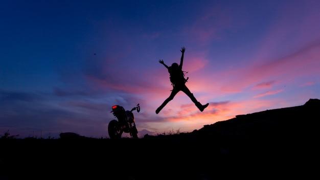 Homme et moto au coucher du soleil