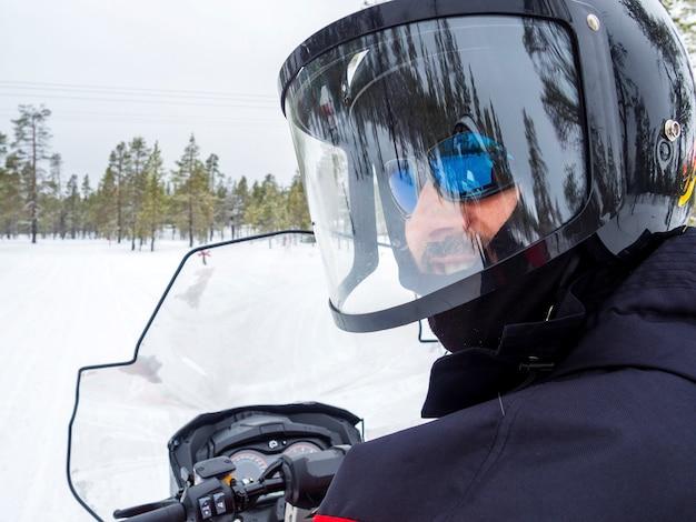 Un homme en motoneige en montagne d'hiver