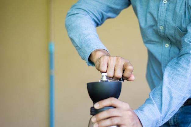 Un homme moud les grains de café avec un batteur à main.