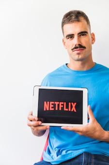 Homme avec moustache montrant le logo netflix