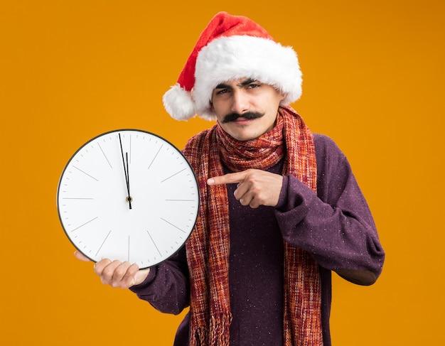 Homme moustachu portant un bonnet de noel avec une écharpe chaude autour du cou tenant une horloge pointée avec l'index sur elle, l'air confus et mécontent debout sur un mur orange