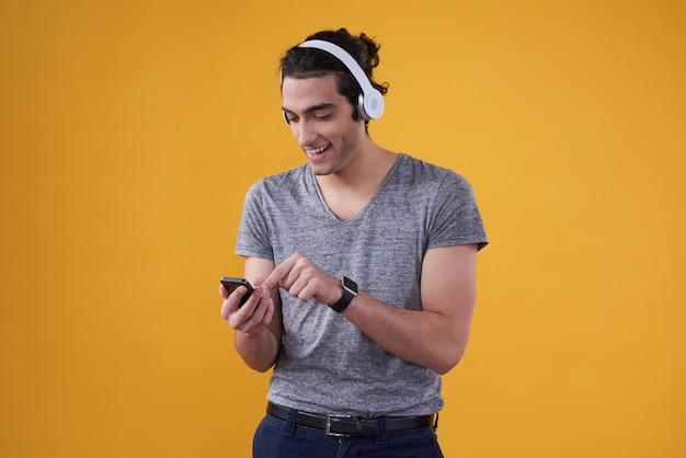 Homme moyen-oriental, jouer de la musique sur téléphone isolé