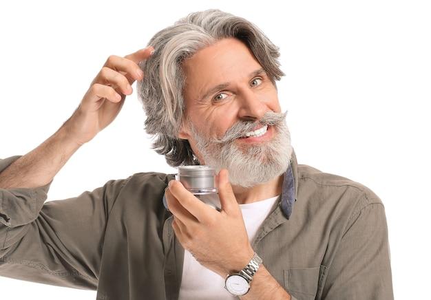Homme mûr à l'aide de cosmétiques pour le traitement de la perte de cheveux sur fond blanc