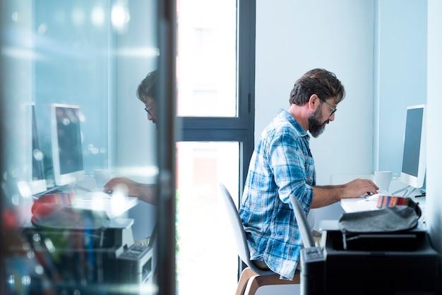 Homme mûr assis sur une chaise devant l'ordinateur et tapant sur le clavier tout en travaillant, homme d'affaires travaillant sur le bureau de l'ordinateur. profil d'un homme occupé à travailler sur un ordinateur à la maison du bureau