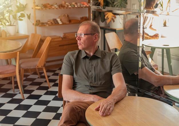 Homme mûr assis à une table en bois dans un café élégant et moderne avec des plantes de meubles en bois et des miroirs...