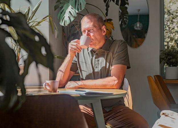 Homme mûr assis à table en bois dans un café moderne avec une tasse de café parmi les plantes